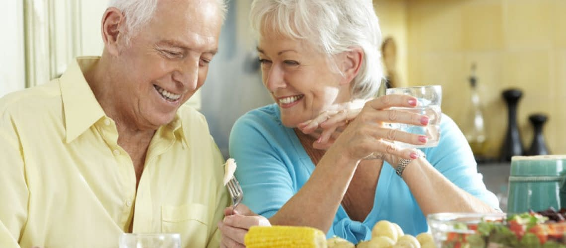 Dental Implant Patients Smiling Together During Dinner