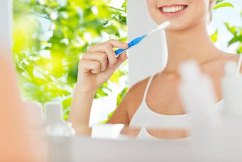 A woman brushing her teeth with a bright & white background