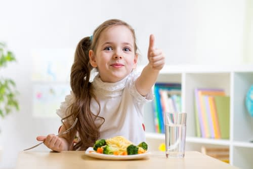 A child eating healthy sticking up her thumb