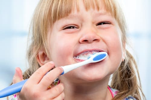 A little girl smiling while brushing her teeth
