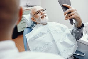 man smiling in mirror at dentist office