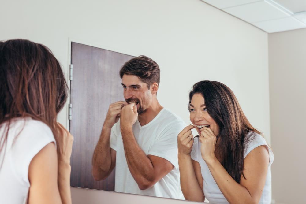 A couple flossing their teeth