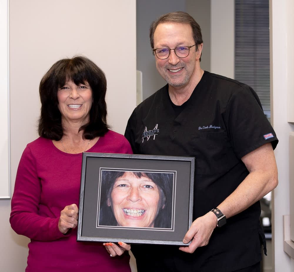 dr medgaus with female patient after dental implants