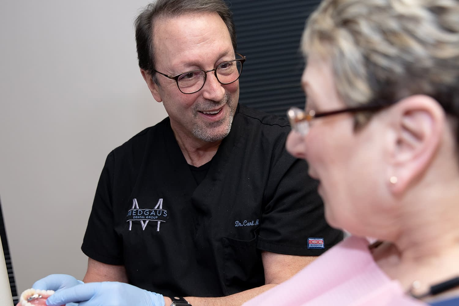 Dr. Medgaus speaking to patient about dental implants