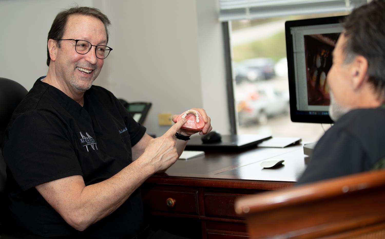 dr medgaus holding a dental implant model