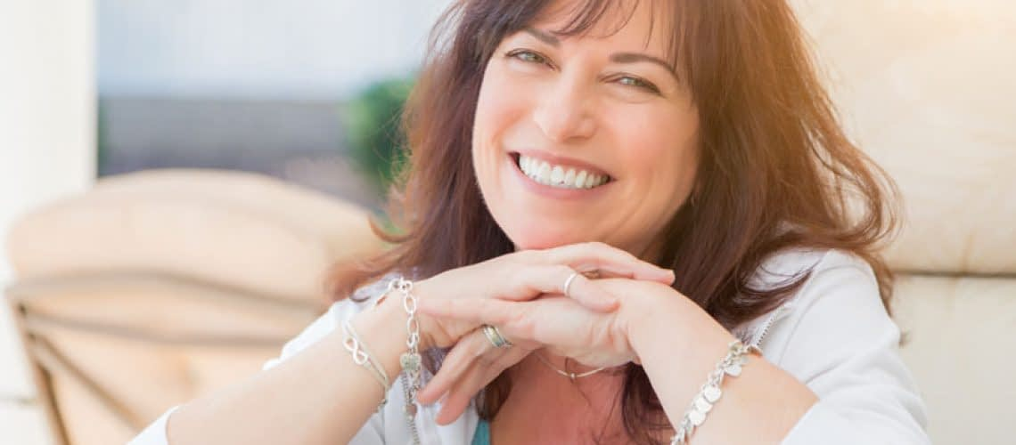 a patient smiling after her all on 4 dental implant procedure