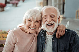 elderly couple smiling after their implant supported denture procedures
