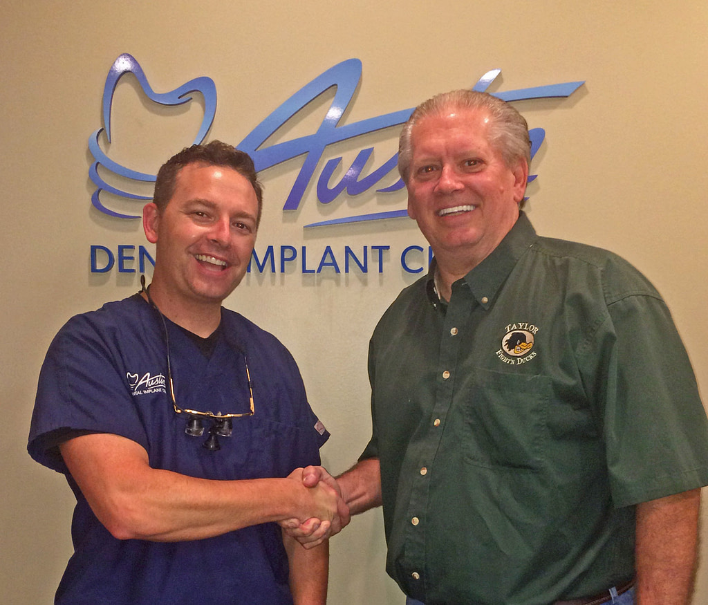 Dr. Dan Holtzclaw shaking hands with a dental patient
