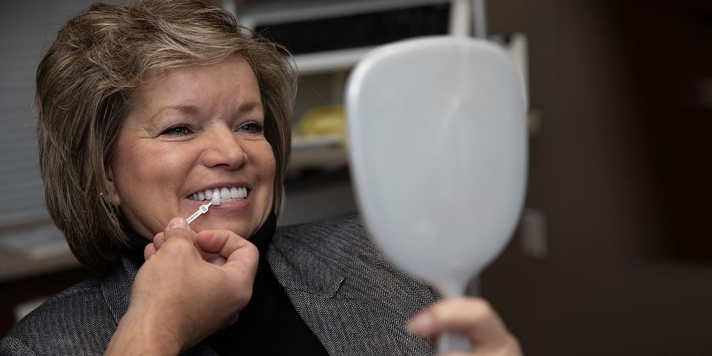 dental veneers patient looking in the mirror
