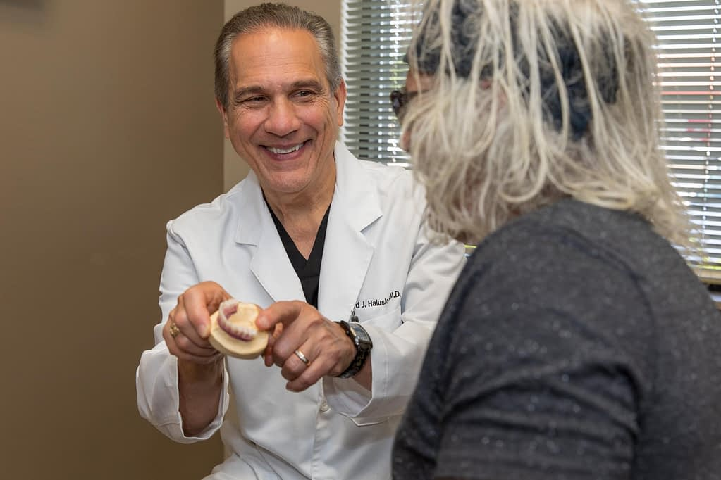 oral surgeon dr halusic showing a dental implant model to older male patient