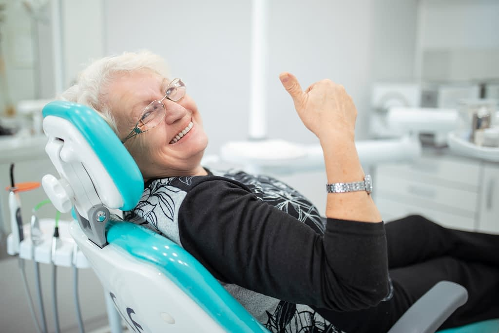 smiling elderly woman in dentist chair