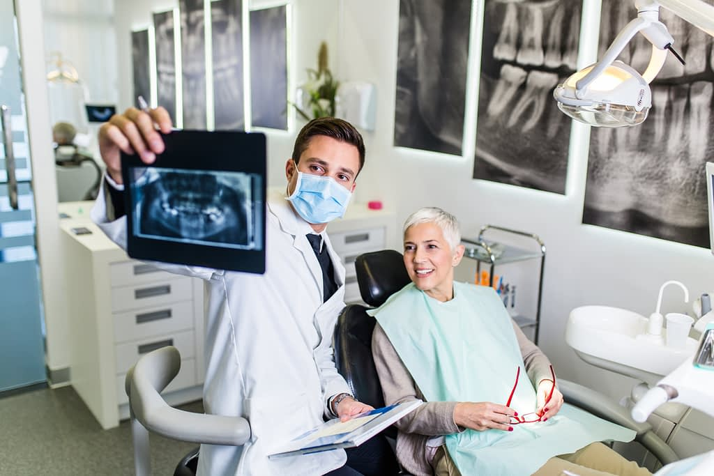 Dentist showing elderly woman x-ray results
