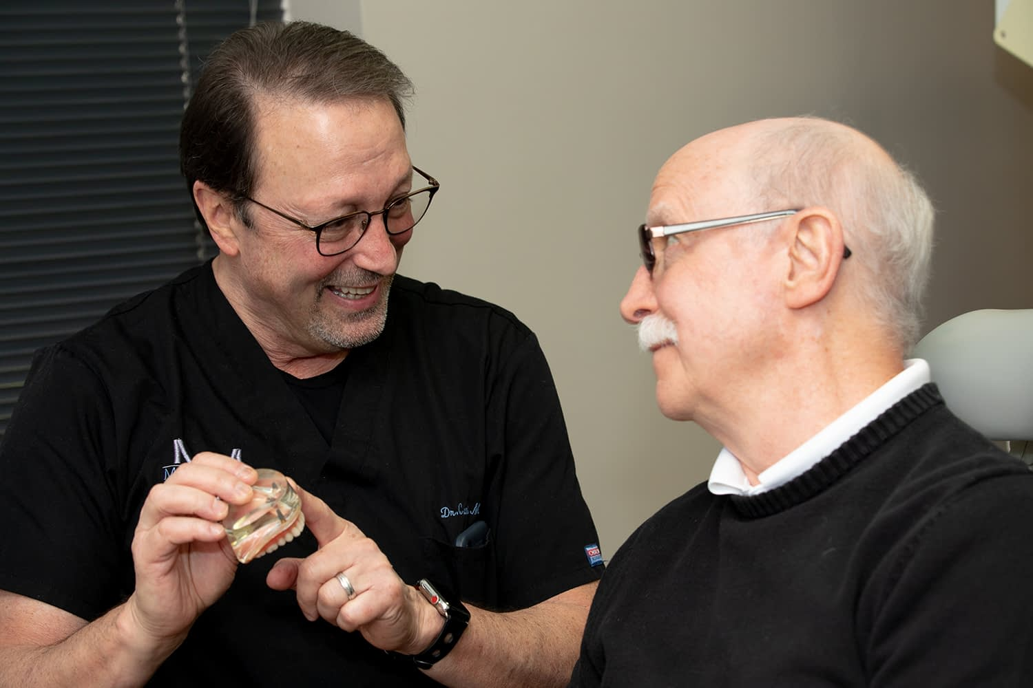 dr. medgaus showing a patient dental implants