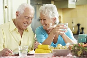 Dental Implant Patients Smiling And Eating Dinner Together