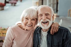 a couple smiling with their all on 4 dental implants