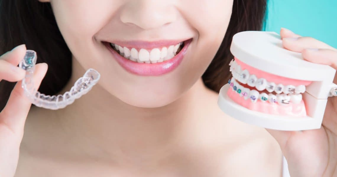 Dental Patient Smiling While Holding Up Her Invisalign